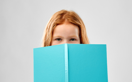 smiling red haired girl reading book Stock Photo - 120496657