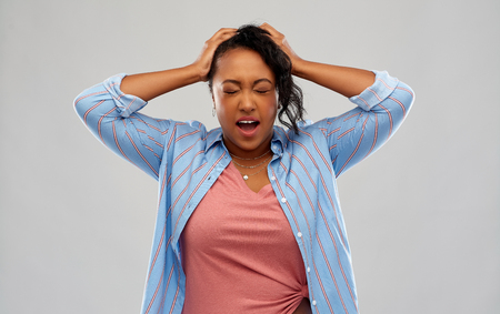 stressed african american woman holding to head Stock Photo