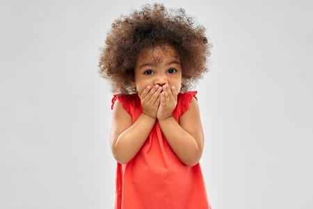verwirrtes afroamerikanisches Mädchen, das den Mund bedeckt Standard-Bild
