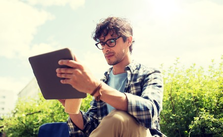 A man in glasses with tablet pc on city street