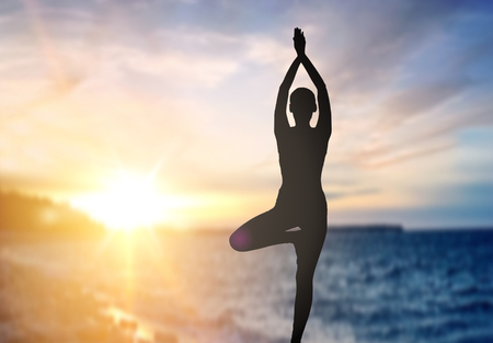 Silhouette of woman making yoga over sea sunset
