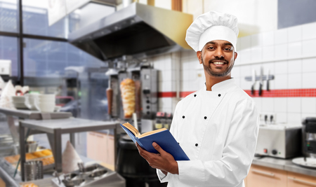 Happy Indian chef with cookbook at kebab shop