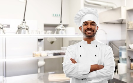 Happy Indian chef in toque at restaurant kitchen Stockfoto