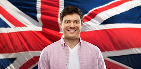 Smiling young man over British flag background