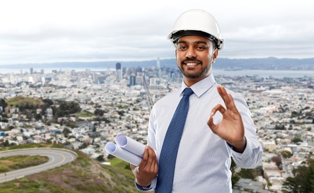 Architect in helmet with blueprints showing ok Stock Photo