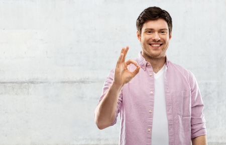 Smiling young man showing ok hand sign Stock Photo