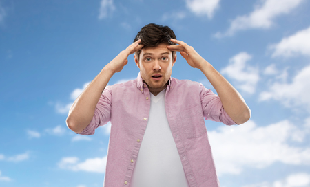 A man touching his head over blue sky background
