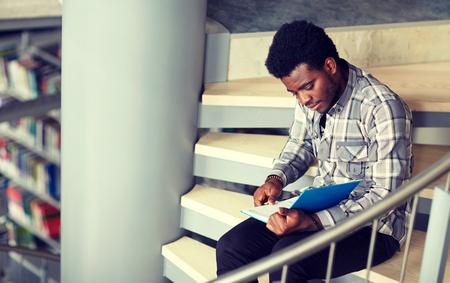 Afrikanischer Studentenjunge oder Mann, der ein Buch in der Bibliothek liest