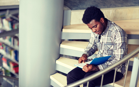 African student boy or man reading book at library Foto de archivo