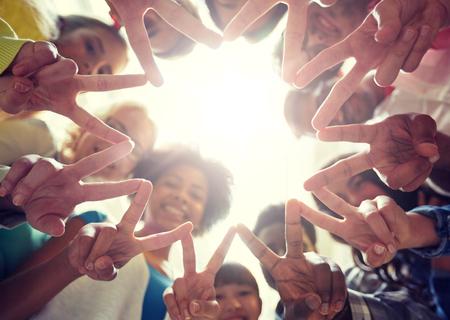 Estudiantes internacionales que muestran la paz o el signo v