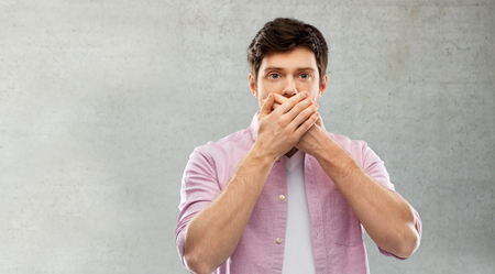 Shocked young man covering his mouth by hands