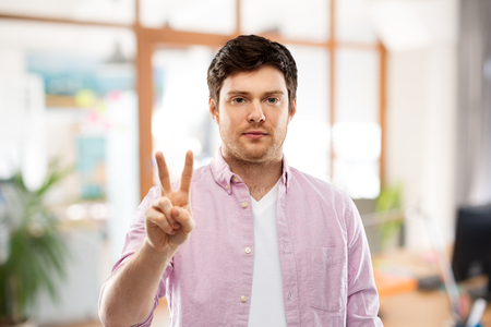 Young man showing two fingers over office Banco de Imagens