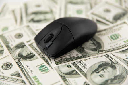 Cerca del ratón de la computadora en dinero en dólares estadounidenses Foto de archivo