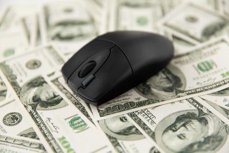 Primo piano del mouse del computer sul denaro in dollari americani Archivio Fotografico