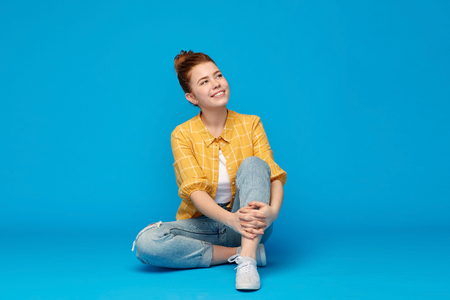 Red haired teenage girl in shirt and torn jeans
