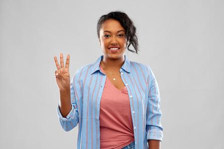 Happy African American woman showing three fingers Archivio Fotografico - 120571272