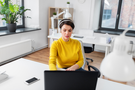 Businesswoman with headphones and laptop at office