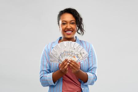 Happy African American woman holding dollar money 스톡 콘텐츠