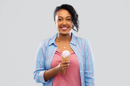 Happy African American woman with ice cream cone Banque d'images - 120571331