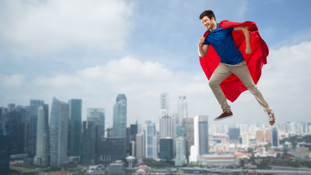 Man in red superhero cape flying in air over city Imagens