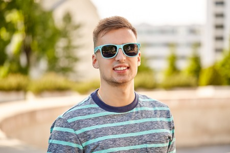 Portrait of young man in sunglasses at summer city
