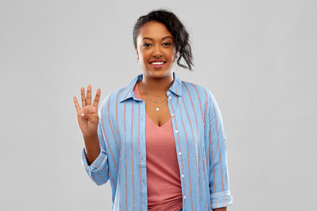 Happy African American woman showing four fingers