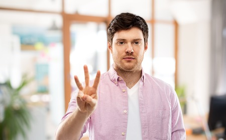 Young man showing three fingers over office Archivio Fotografico - 120571374