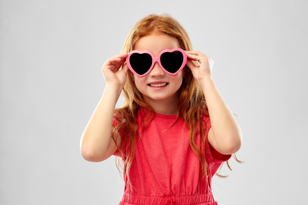 Smiling red haired girl in heart shaped sunglasses
