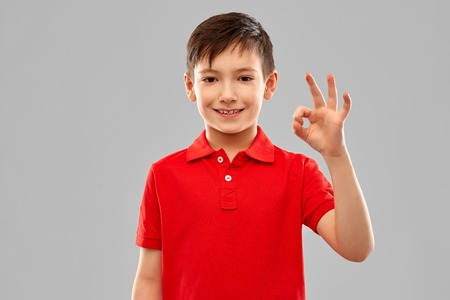 Smiling boy in red t-shirt showing ok hand sign Stock fotó - 120571385