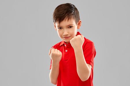 Chico en camiseta roja mostrando puños o boxeo Foto de archivo