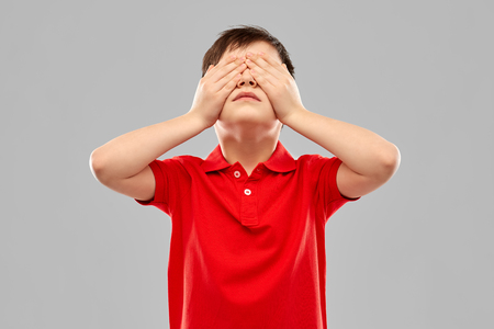 Boy in red t-shirt closing his eyes by hands Imagens