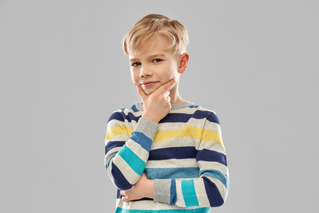 Portrait of thinking boy in striped pullover