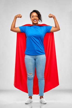 Feliz mujer afroamericana en capa roja de superhéroe Foto de archivo