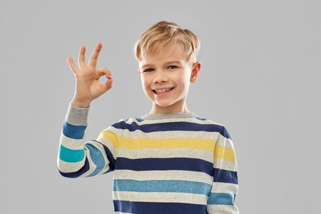 Boy in striped pullover showing ok hand sign