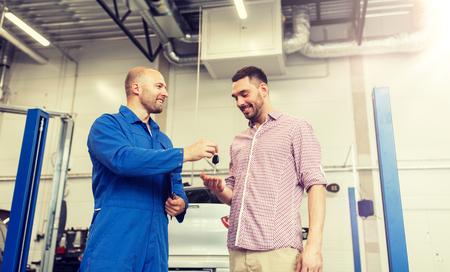 auto mechanic giving key to man at car shop 版權商用圖片