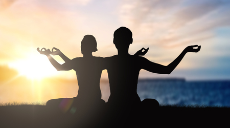 couple doing yoga in lotus pose over sunset