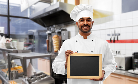 happy indian chef with chalkboard at kebab shop Stockfoto