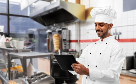 male indian chef with tablet pc at kebab shop