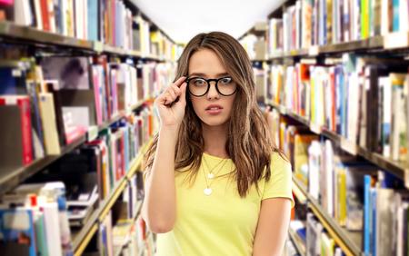 studentessa adolescente con gli occhiali in biblioteca