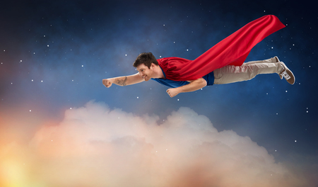 man in red superhero cape flying over night sky