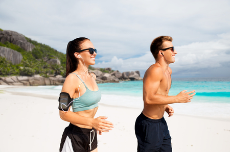 couple with phones and arm bands running on beach