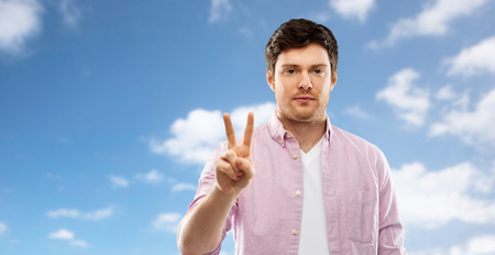 young man showing two fingers over sky Stock Photo