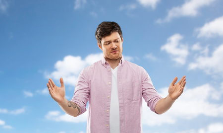doubting man showing size of something over sky Stock Photo