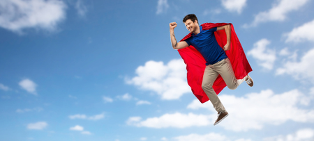 man in red superhero cape flying over sky