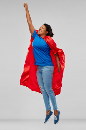 african american woman in superhero cape flying up