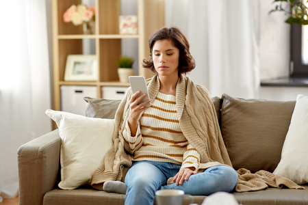sad sick woman in blanket using smartphone at home