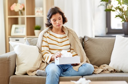 sick woman taking paper tissue from box at home