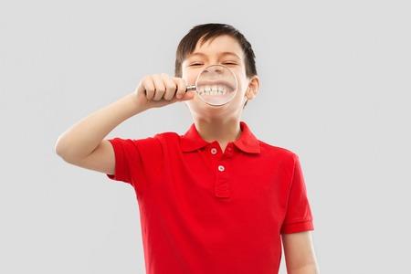 boy showing his teeth through magnifying glass