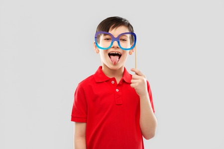 happy boy with big paper glasses showing tongue Stock Photo - 120809674
