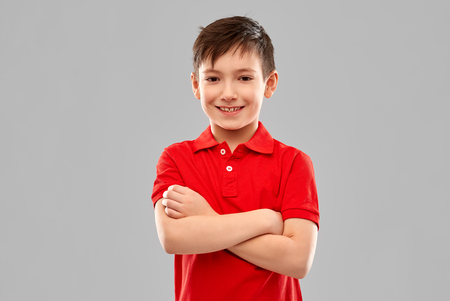 smiling boy in red t-shirt with crossed arms
